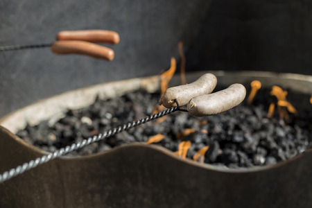 Roasting hot dogs and sausages over the coals of a campfire