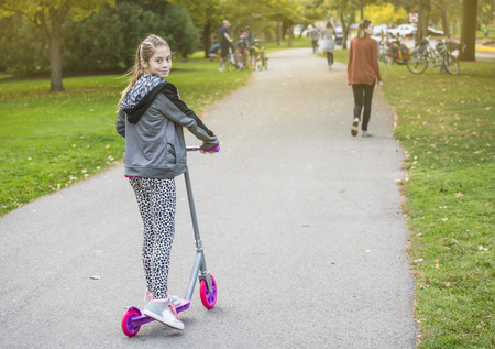 empedrado: Una muchacha que monta junto al aire libre en un camino pavimentado para bicicletas. Sonriendo y divirtiéndose en un parque de la ciudad al aire libre