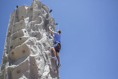 Man rotsklimmen buitenshuis op een kunstmatige muur