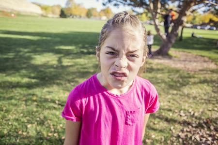 Een klein meisje met een emotionele uitbarsting op de schoolwerf. Ze is boos en boos en toont sterke emoties