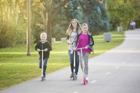 mini bike: A women and her children riding together outdoors on a paved bike pathway. Smiling and having fun together at a outdoor nature park Stock Photo