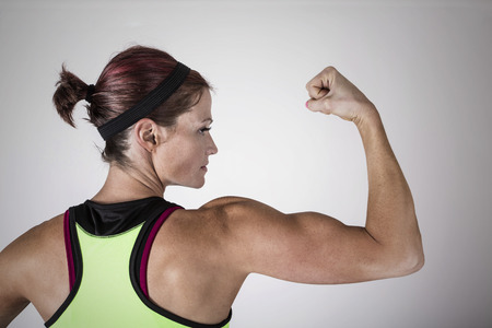 Beautiful Strong Muscular Woman Flexing Her Biceps And Arm Muscles ...