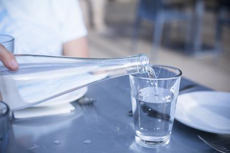 Gieten Gedistilleerd water in een helder glas in een restaurant Stockfoto