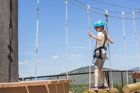Meisje klimt op een buitentouwbaan Stockfoto