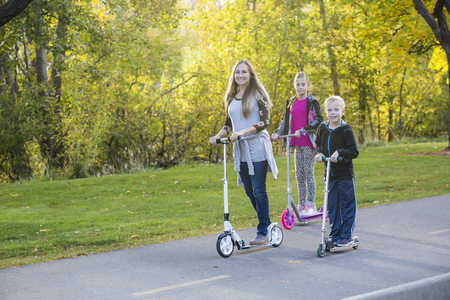 Family riding together outdoors on a paved bike pathway. Family is smiling and having fun together at a outdoor nature park