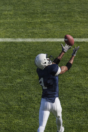 Football action photo of athlete catching a touchdown pass. View from above