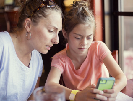 Concerned and cautious mother is looking at her daughter using her smart phone. She is watching closely at and teaching her daughter how to user her smart phone Stock Photo