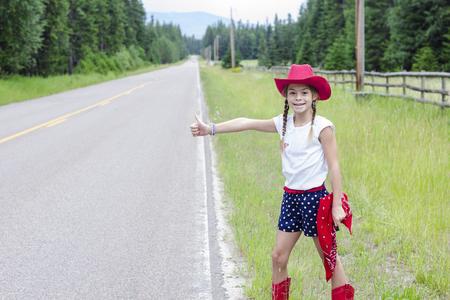 Leuke kleine veedrijfster die op een eenzame weg een ritje probeert te haken. Knip haar duim uit en probeer ergens naar toe te rijden. Homeward gebonden