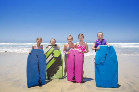 Cute group of kids standing by a boogie boards at the beach while playing in the ocean on vacation. Lots of copy space. photo