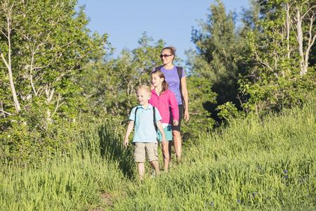 Een vooraanzicht van een jong gezin wandelen samen in een prachtige berg weide trail. Veel kopieerruimte. Foto van volledige lengte