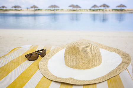 Zon hoed en zonnebril op een lounge stoel op het strand