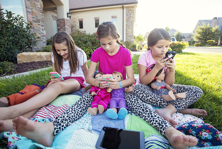 Three little girls playing on their smart phones instead of talking photo
