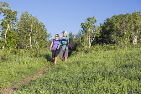 Actieve, middelbare leeftijd paar hand in hand wandelen samen langs een bergspoor. Veel exemplaarruimte