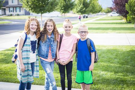 Vier schoolkinderen gaan in de ochtend naar school Stockfoto