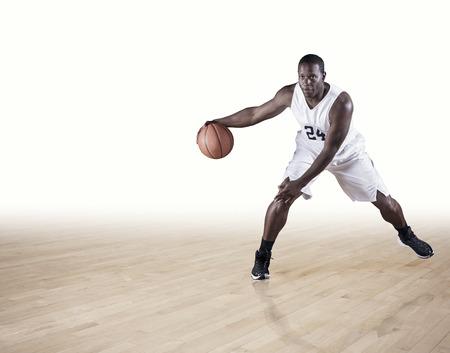 Een sterke atletische professionele basketbalspeler die de rechtbank dribbelt dribbelt. Schone witte achtergrond. Veel exemplaarruimte