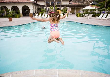 小さな女の子が大きな裏庭のプールに飛び込みます。後ろからを表示します。同じように彼女は暖かい夏の日に水に飛散する準備ができてを撮影し