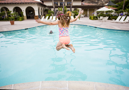 Little girl jumping into a big backyard swimming pool. View from behind. Photo taken just as she is ready to splash into the water on a warm summer day 스톡 콘텐츠
