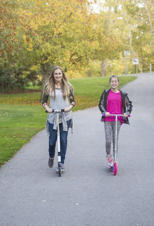 Een gelukkig meisje en haar moeder rijden buitenshuis op een verharde fietsroute. Glimlachend en plezier samen in een buitenstadspark Stockfoto