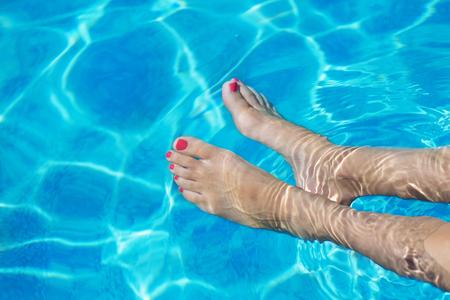 uñas pintadas: Hermosos pies y pies en la piscina Foto de archivo