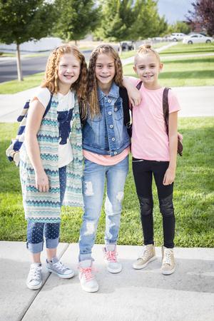 Drie schattige lachende meisjes met rugzakken op school in de ochtend Stockfoto