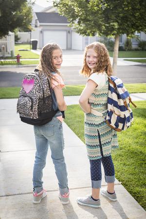 Twee schattige schoolmeisjes gaan naar school