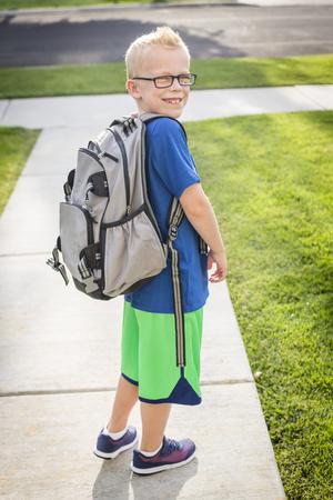 Leuke basisschoolse jongen die een rugzak in de ochtend naar school gaat Stockfoto