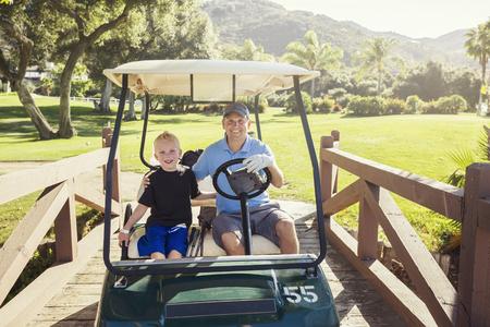 아버지와 아들이 함께 골프 카트 여름 날 타기에 함께 골프 스톡 콘텐츠