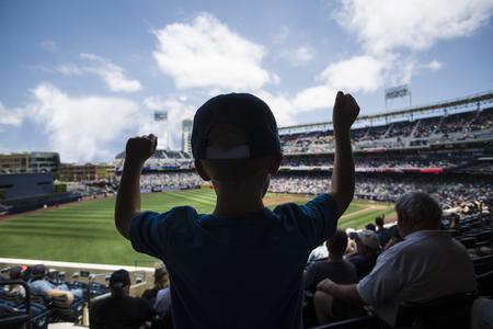 서 야구 경기에서 응원하는 아이. 뒤에서 실루엣보기