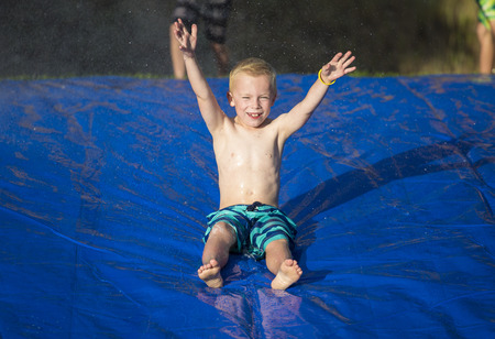 Young boy sliding down a slip and slide outdoors Stock Photo
