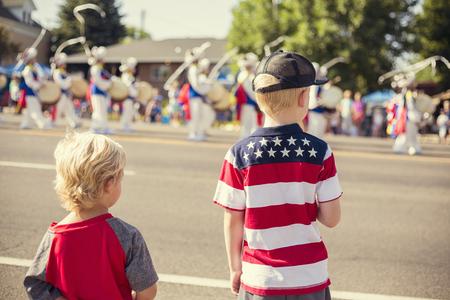 Niños viendo un desfile del Día de la Independencia en un día de verano Foto de archivo - 74625917