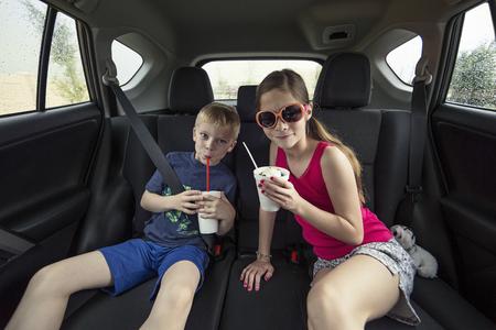 自分の車の後ろに御馳走を食べる子供たち