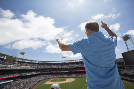 Man fan staan en juichen tijdens een honkbalwedstrijd