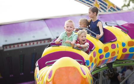 Les enfants sur un tour de montagnes russes passionnant à un parc d'attractions