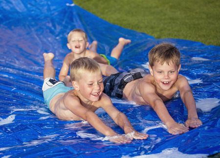 Happy kids playing on a slip and slide outdoors