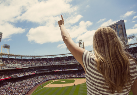 Woman standing and cheering at a baseball game 免版税图像 - 74564179