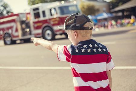 미국의 작은 마을에서 독립 기념일 퍼레이드 동안 퍼레이드 행렬 도중하여 소방차 드라이브를보고 소년 스톡 콘텐츠