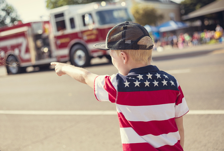 Boy watching a firetruck drive by during a parade procession during an Independence Day parade in a small town in the USA Foto de archivo