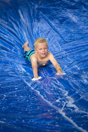 Smiling boy playing on a slip and slide outdoors photo