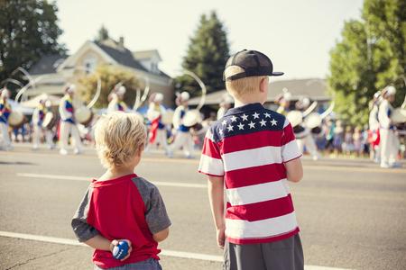 Niños viendo un desfile del Día de la Independencia Foto de archivo