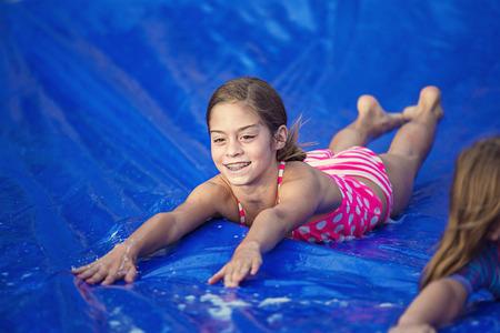 Smiling little girl sliding down an outdoor slip and slide