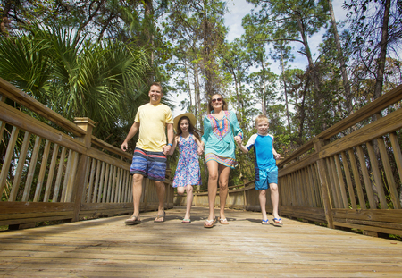 Happy young family having fun together while on a tropical island vacation photo