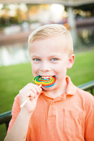 Cute young boy licking a large colorful lollipop outdoors photo