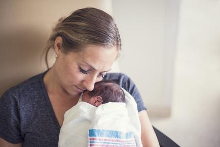Moeder die haar pasgeboren voorbarige baby in het ziekenhuis houdt Stockfoto