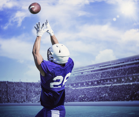 American Football Player Catching a touchdown Pass in a large outdoor football stadium Banco de Imagens