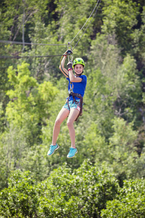 Smiling little girl riding a zipline through the forest