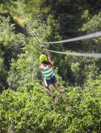 Teen girl riding a zip line through the forest. View from behind