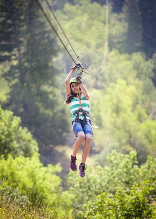 Gelukkig divers meisje die een pitlijn in een weelderig bergbos berijden terwijl op familievakantie