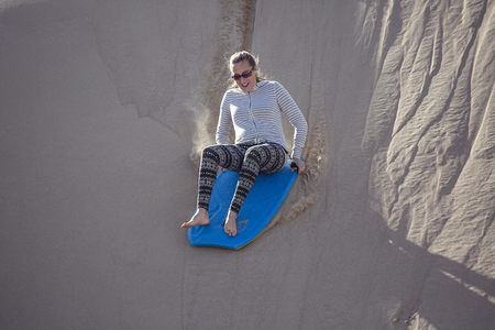 Thrill seeking woman Playing in the Sand Dunes Outdoor Lifestyle Banque d'images