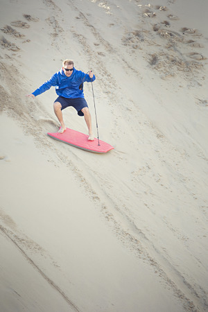 Opgewonden medio volwassen man rijdt op een plank in een zandduinheuvel met plezier buiten spelen terwijl hij op vakantie is.