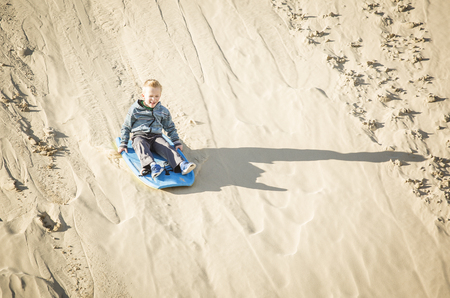 Thrill seeking boy Playing in the Sand Dunes Outdoor Lifestyle